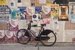 Bicycle against poster covered wall