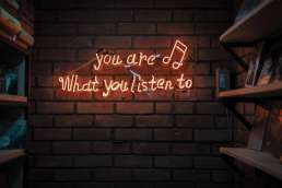 Red neon lights that form the words 'you are what you listen to'