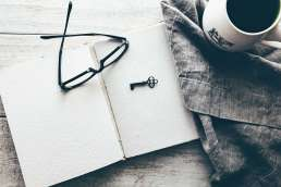 Blank notebook with glasses, a key, and a coffee cup next to it