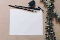 Blank paper with calligraphy pens and leaves next to paper