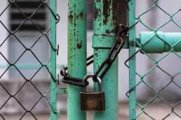 Metal fence locked with lock and chain