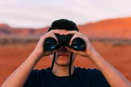 Man facing camera looking through binoculars with desert in background behind him