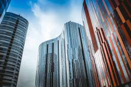 Tall glass windowed buildings and blue cloudy sky
