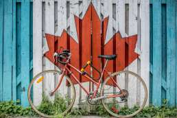 Red bicycle next to painted mural of red maple leaf