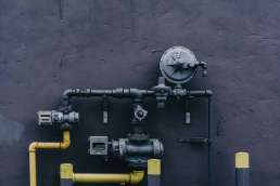 Yellow and gray pipes against gray wall