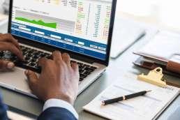 Man typing on computer displaying data