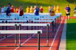 Picture of hurdles with people in background running towards them