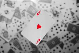 Red ace playing card with black and white playing cards in background