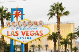Welcome to Las Vegas sign with a hotel and palm trees in the background