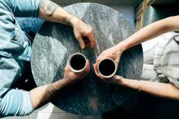 Two people sitting across from one another, holding coffee cups