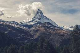 Photo of mountain with evergreen trees and clouds in the background