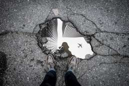 Feet and puddle with puddle reflecting a person, buildings, and a plane flying overhead