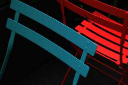 Red and blue chairs against black background
