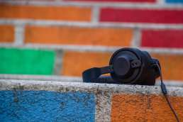Headphones with multi-colored painted bricks in background