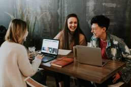 Three people laughing around a table with laptops
