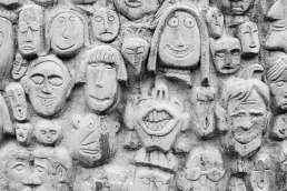 Wall of clay sculpted faces