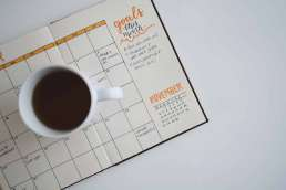 Calendar open with coffee mug filled with coffee sitting on it