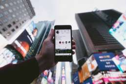 Person holding phone open to Instagram up against city background