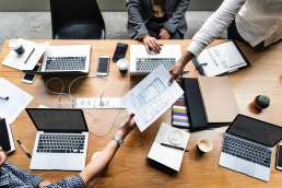 Group of people working together using laptops and files