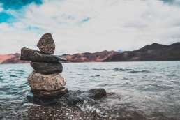Rocks stacked in river with mountains and cloudy sky in background