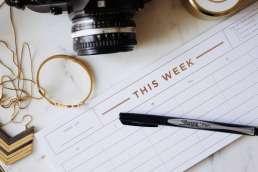 Empty weekly calendar, a pen, and a camera