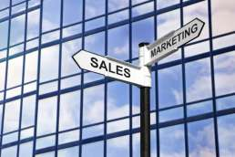 Sign saying sales and marketing against glass building