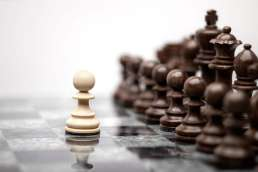 A single light colored pawn against all of the dark colored chess pieces