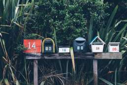 Row of mailboxes against green foliage
