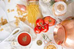 Ingredients and supplies for making pasta scattered on table