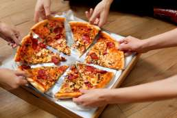 Six hands each grabbing a slice of pizza from the box