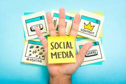 Hand surrounded by sticky notes about social media