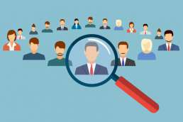 Graphic of magnifying glass hovering over illustrated icon of man in business suit out of a large group of people