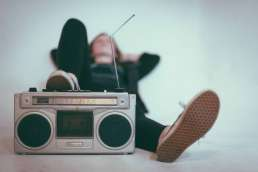 Person laying down with foot propped up on boombox