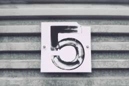 Number 5 painted on sign against metal wall