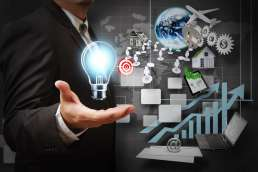 Man holding out hand with graphic of lightbulb, target, and charts floating around