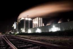 Photo of factory at night with lights on taken from rail road tracks