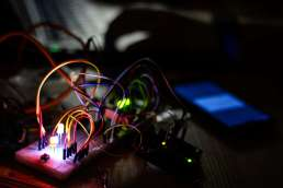 Multi-colored wires plugged into a glowing circuit board