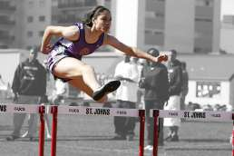 Woman jumping over hurdles with her in color and the background in grayscale