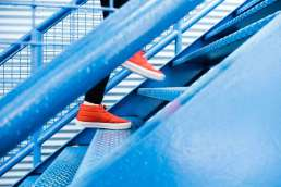 Person in red shoes and black leggings climbing blue stairs