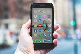 Person holding iPhone opened to apps options