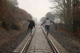 Two people walking on rail road tracks surrounded by trees and fog