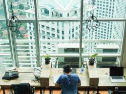 Man doing work on computer at wooden desk in front of glass windows overlooking cityscape