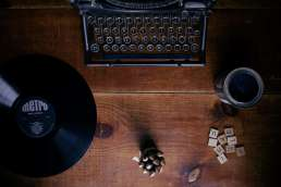 Typewriter, record, and scrabble pieces on wooden desk