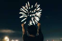 Photo of man facing away from camera with arms up pointing at firework exploding in night sky
