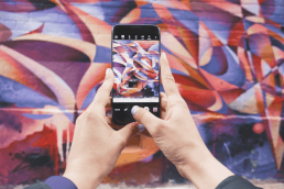 Photo of person's hands holding phone taking photo of a mural
