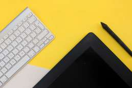 Tablet, electronic pen, and keyboard against yellow background
