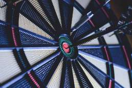 Dart board with dart in the bullseye