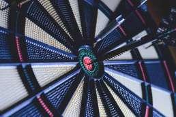 Dart board with dart in the bullseye