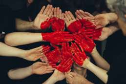 People with red painted hands holding their hands together to form a painted heart