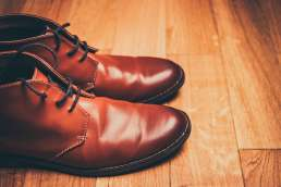 Brown leather shoes on wooden floor